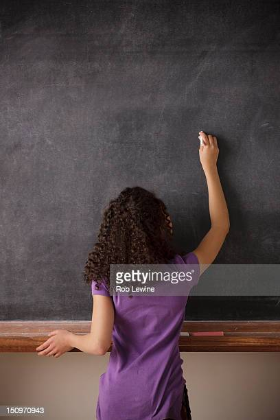 USA, California, Los Angeles, Portrait of schoolgirl (10-11) writing on blackboard
