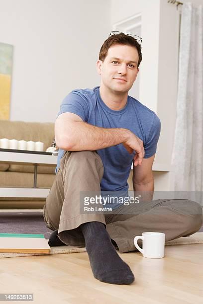 USA, California, Los Angeles, Portrait of smiling mid adult man sitting on floor