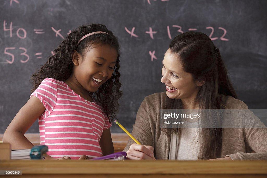 USA, California, Los Angeles, schoolgirl (10-11) and teacher with blackboard in background