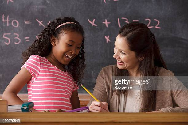 USA, California, Los Angeles, schoolgirl (10-11) and teacher with blackboard in background