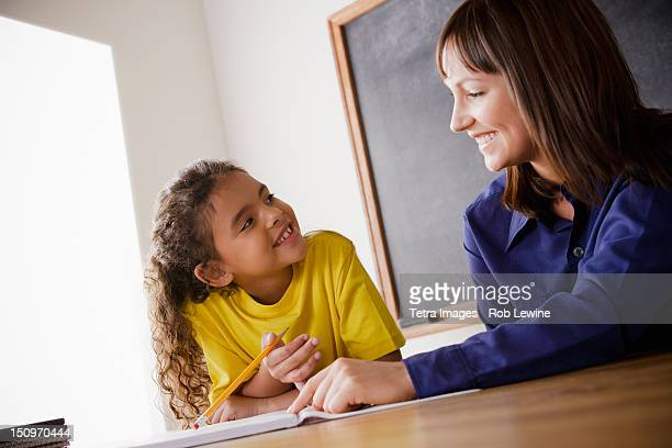 USA, California, Los Angeles, Schoolgirl writing with teacher in classroom