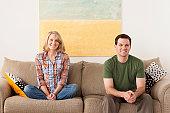 USA, California, Los Angeles, Smiling mid adult couple sitting on sofa