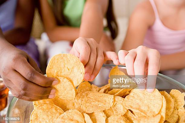 USA, California, Los Angeles, Three girls (10-11) reaching for crisps