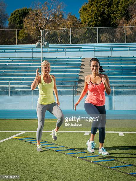 USA, California, Los Angeles, Two women jumping along rope ladder