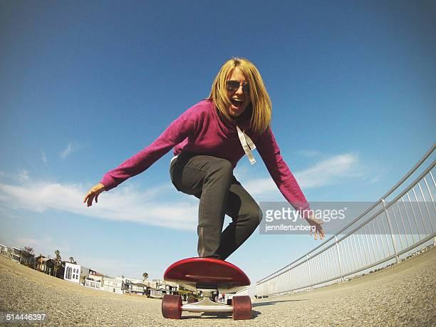 'USA, California, Los Angeles, Venice Beach, Young woman skateboarding next to beach'