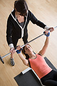 USA, California, Los Angeles, Woman lifting barbell while instructor assisting her