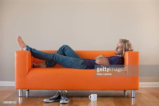 USA, California, Los Angeles, Young man lying on sofa