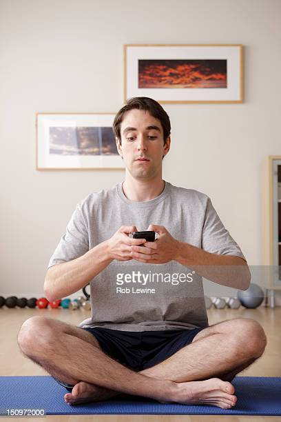 USA, California, Los Angeles, Young man meditating with mobile