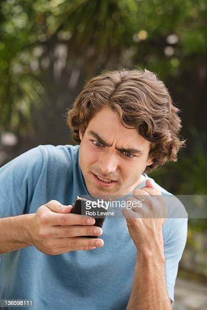USA, California, Los Angeles, Young man text-messaging and shaking fist