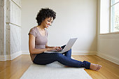 USA, California, Los Angeles, Young woman sitting in room using laptop