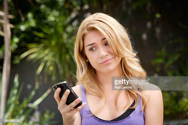 USA, California, Los Angeles, Young woman text-messaging, with facial expression
