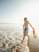 USA, California, Malibu, Attractive young woman walking on sandy beach