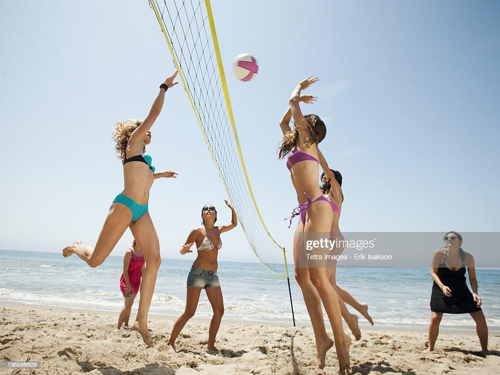 USA, California, Malibu, Group of young women playing beach volleyball