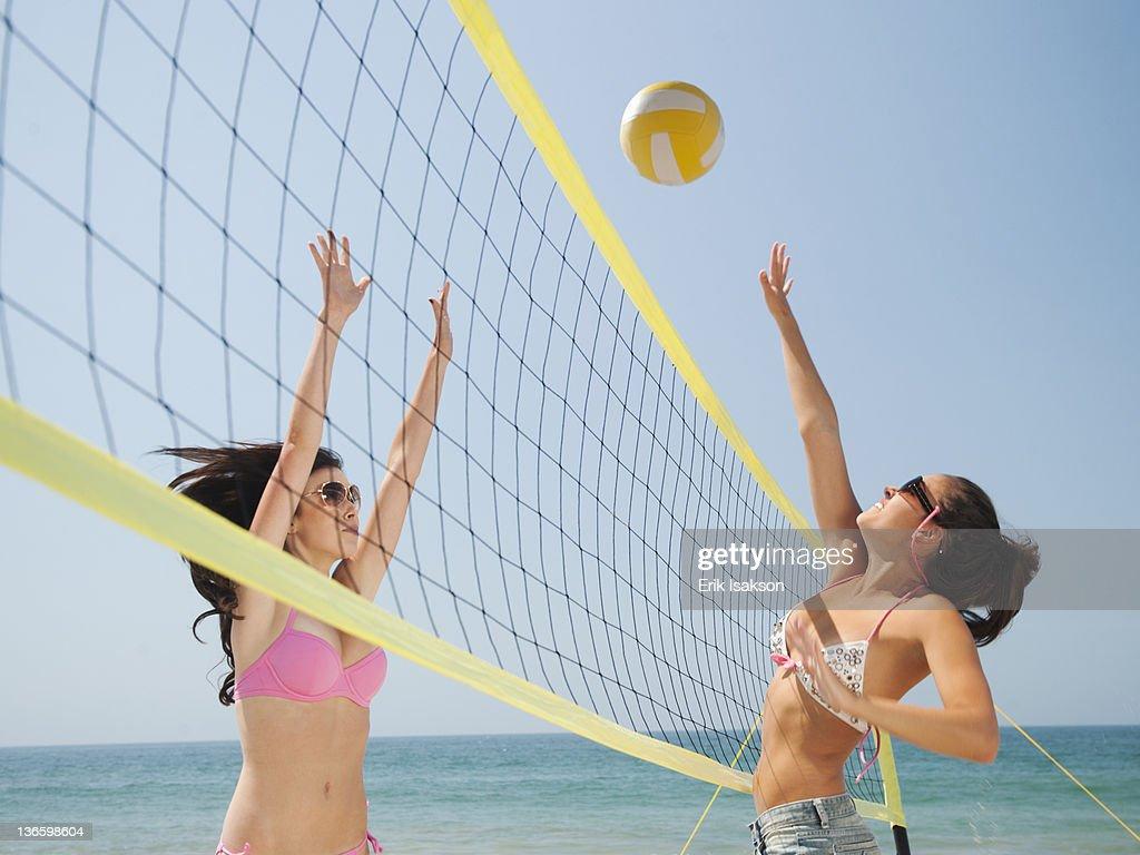 USA, California, Malibu, Two attractive young women playing beach volleyball