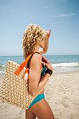 USA, California, Malibu, young attractive woman carrying straw bag on sandy beach
