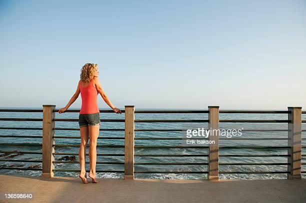 USA, California, Malibu, Young attractive woman contemplating seascape from terrace