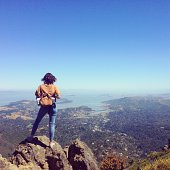 USA, California, Marin County, Mill Valley, Young woman standing on mountain overlooking San Francisco