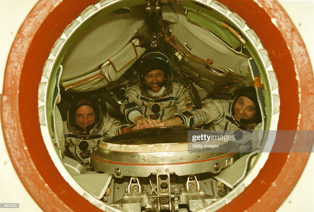 California millionaire Dennis Tito, left, and Russian cosmonauts Talgat Musabayev, center, and Yuri Baturin put their hands together as they pose for the photographer inside the SoyuzTM training capsule in Star City April 12, 2001 outside Moscow, Russia. Russian officials gave the green light to the California millionaire to become the first tourist in space despite reservations from NASA.