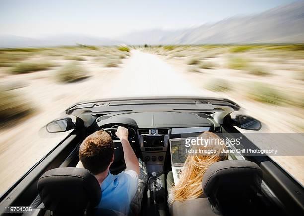 USA, California, Palm Springs, Coachella Valley, San Gorgonio Pass, Couple driving through desert in convertible car
