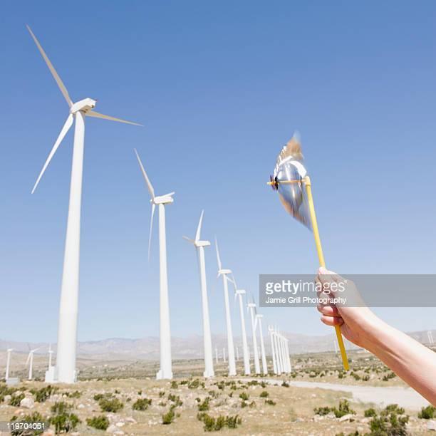 USA, California, Palm Springs, Coachella Valley, San Gorgonio Pass, Woman's hand holding pinwheel against blue sky and wind turbines