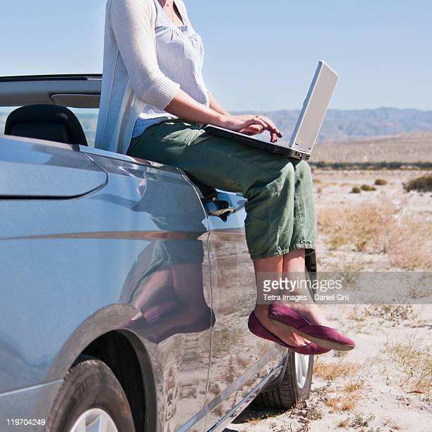 USA, California, Palm Springs, Woman sitting on side of convertible car in desert, using laptop