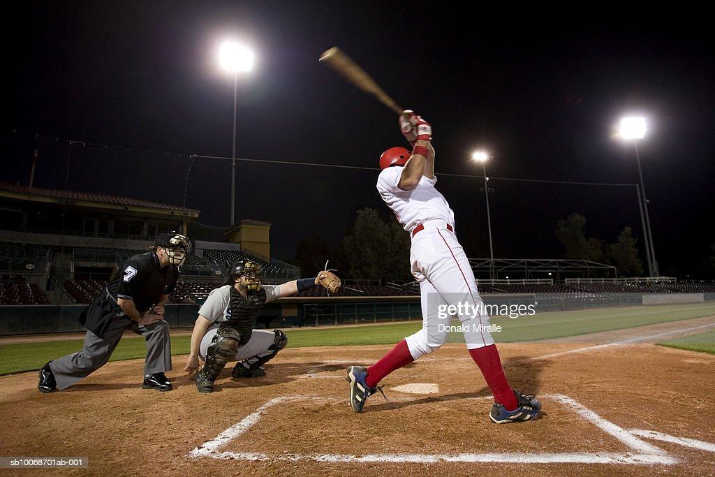 USA, California, San Bernardino, baseball players with batter swinging : Stock Photo