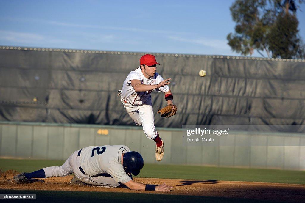 USA, California, San Bernardino, baseball runner sliding for base and baseman leaping for catch : Stock Photo