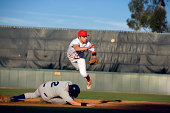 USA, California, San Bernardino, baseball runner sliding for base and baseman leaping for catch