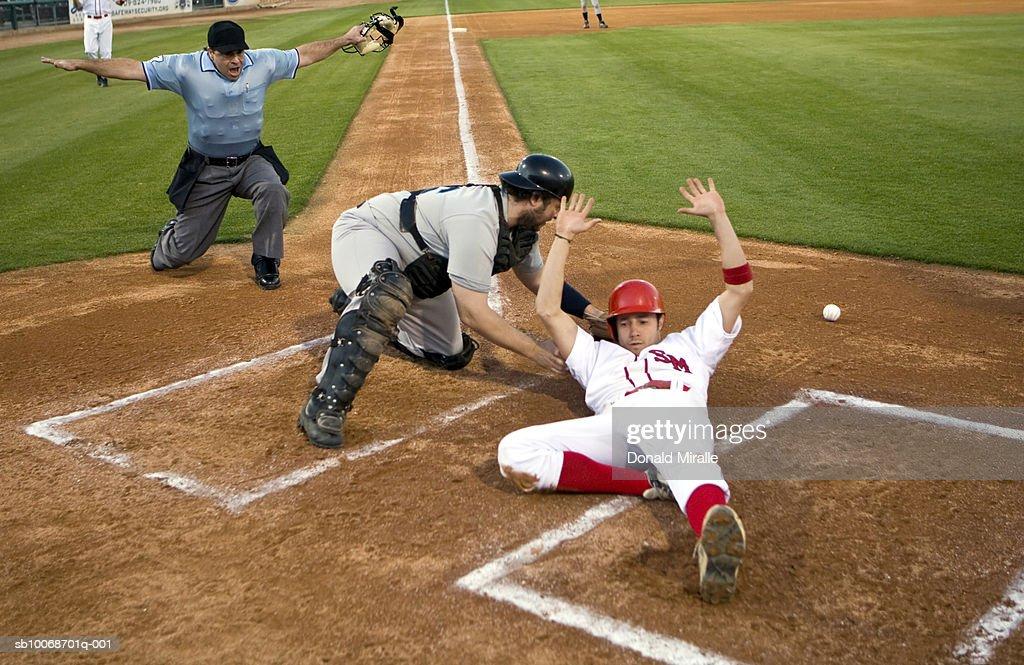 USA, California, San Bernardino, baseball runner sliding safely into home base : Stock Photo
