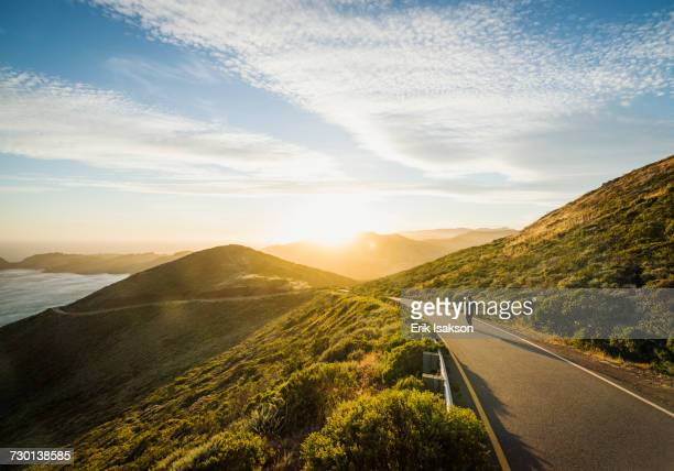 USA, California, San Francisco, California, Man walking on coastline road at sunset