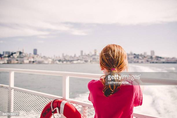 USA, California, San Francisco, Girl (6-7) on ferry looking at city skyline