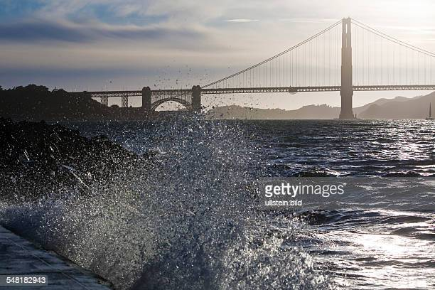 USA California San Francisco Golden Gate Bridge at evening with with splashing waves of the San Francisco Bay in the foreground