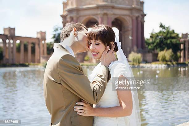 USA, California, San Francisco, Groom kissing bride in park