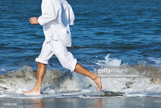 USA, California, San Francisco, Low section of man running ankle deep in sea