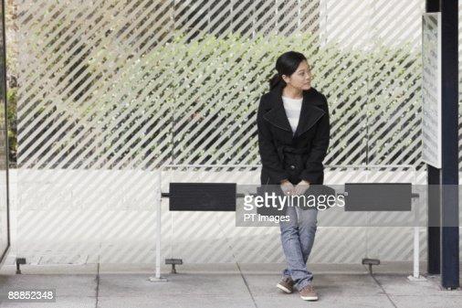 USA, California, San Francisco, young woman waiting at bus stop