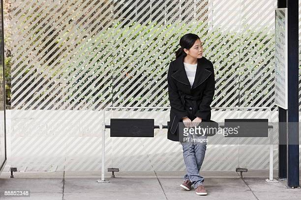 USA, California, San Francisco, young woman waiting at bus stop