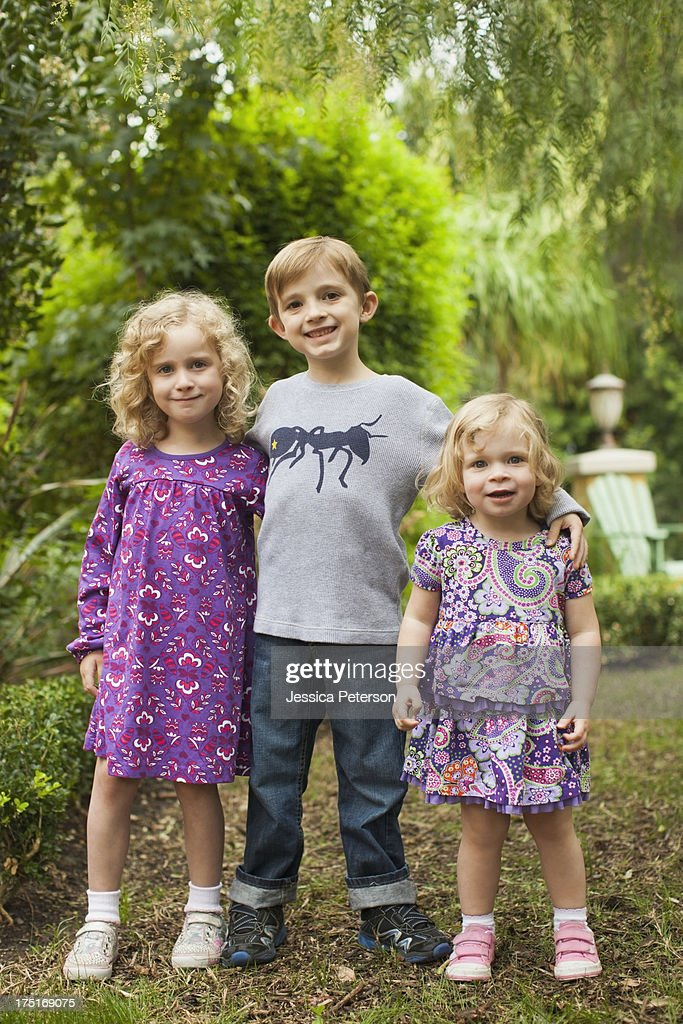 USA, California, San Juan Capistrano, Brother (6-7) and sisters (2-3,4-5) posing together in garden  : Stock Photo