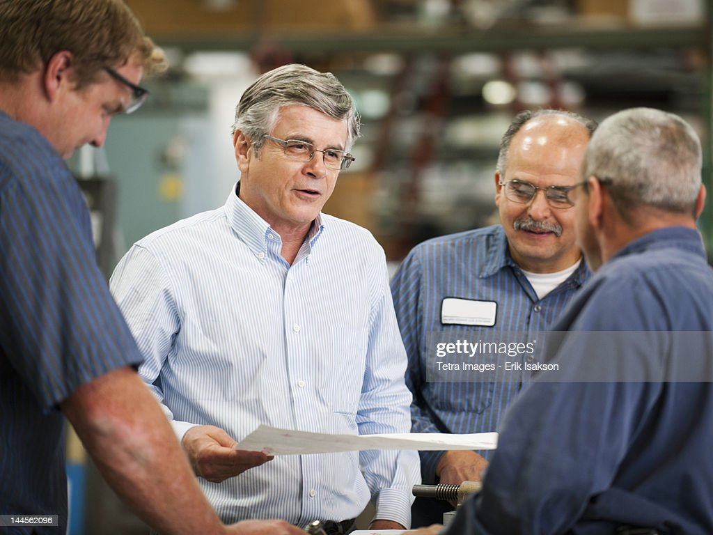 USA, California, Santa Ana, Businessman and workers talking in factory : Stock Photo