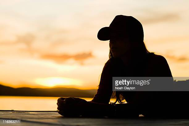 USA, California, Silhouette of young woman relaxing on beach at sunset