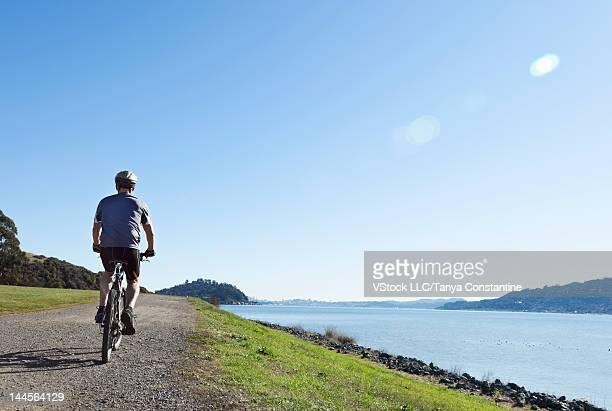 USA, California, Tiburon, Man riding bike along lakeshore