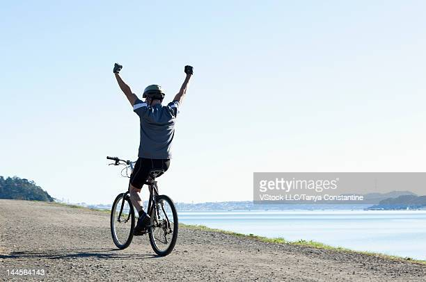 USA, California, Tiburon, Man riding bike along lakeshore with arms up