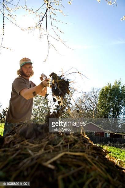 USA, California, young man moving compost on organic farm