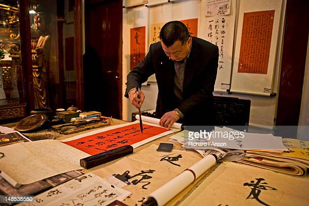 Caligraphy artist painting scroll at Jade Buddha Temple.
