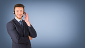 Smiling call center employee during a telephone conversation on blue background