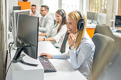Call center operators.Young beautiful business woman with headset working on computer in office with colleagues in the background.