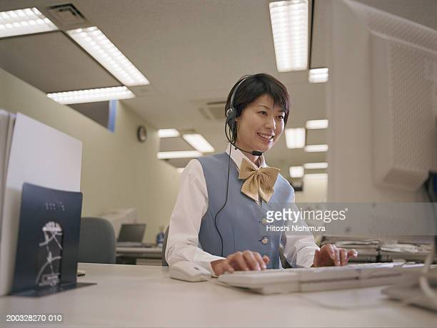 Call centre executive using desktop pc, smiling, low angle view