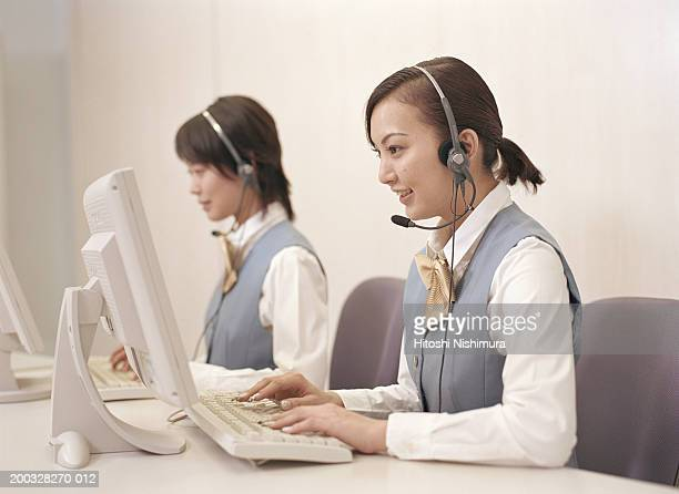 Call centre executives using desktop pc, smiling, side view