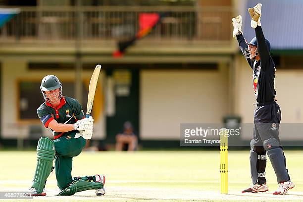 Callan Morse of Tasmania sweeps as Damon Egan appeals for LBW during the Imparja Cup match between Tasmania and Victoria at Traeger Park on February...