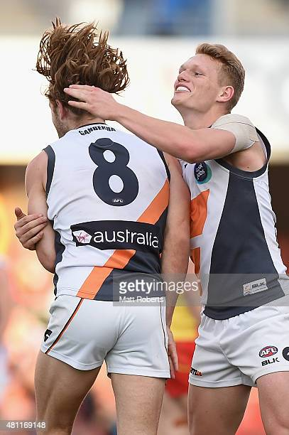 Callan Ward of the Giants celebrates kicking a goal with Adam Treloar during the round 16 AFL match between the Gold Coast Suns and the Greater...