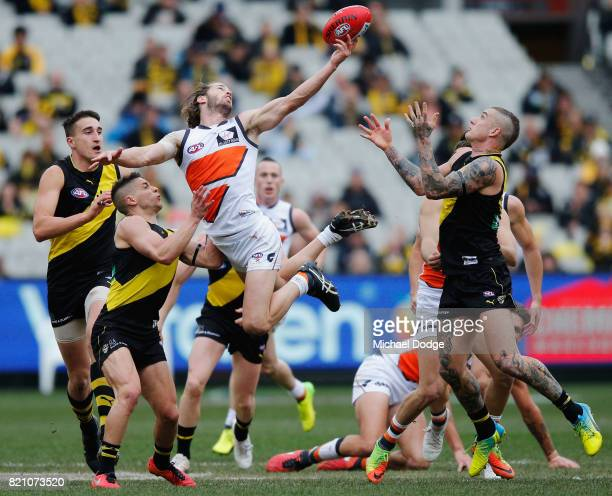 Callan Ward of the Giants gathers the ball from Dustin Martin of the Tigers during the round 18 AFL match between the Richmond Tigers and the Greater...